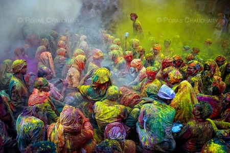 A man standing amidst the cloud of yellow color.  The festival of Holi is a religious festival. People sing bhajans of Radha and Lord Krishna on this day and it marks the beginning of Spring Season in india.  Taken during Holi celebration in India.