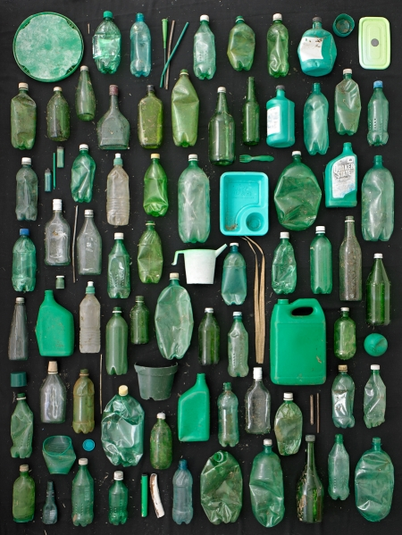 green plastic and glass containers on black background